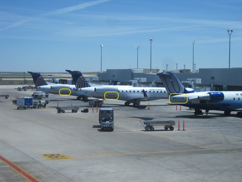 Several airplanes at Denver, with their tail numbers outlined in yellow.
