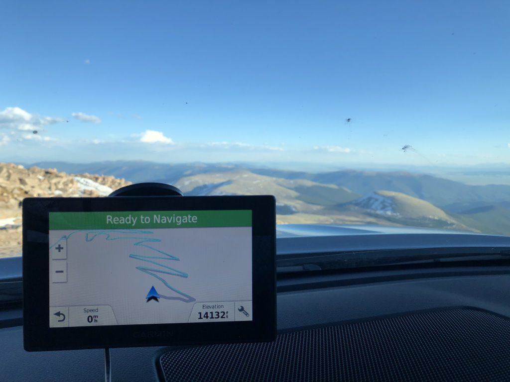 A windshield-mounted GPS on top of Mount Evans, Colorado, showing an elevation of 14132 feet.