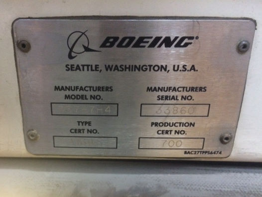 Metal Boeing plaque at the top of an aircraft door frame, showing Manufacturers Serial No. as 33860.